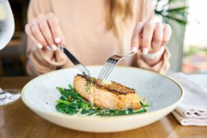 woman eating plate of seafood